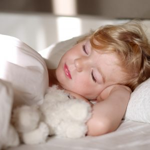 Sweet little child sleeping in bed. Healthy kid, blonde toddler girl, resting in bed in white sunny bedroom.