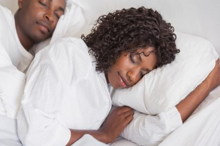 Happy couple sleeping together in bed at home in the bedroom